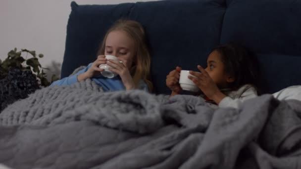 Beteg multi etnikai gyerekek forró teát iszik az ágyban