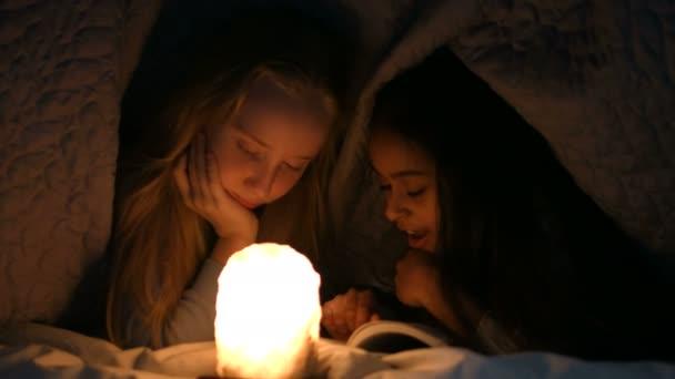 Holčičky, čtení knihy pod deku v noci