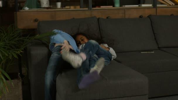 A kanapén játszik két többnemzetiségű kislányok