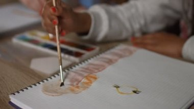 Childrens hands with paintbrushes painting