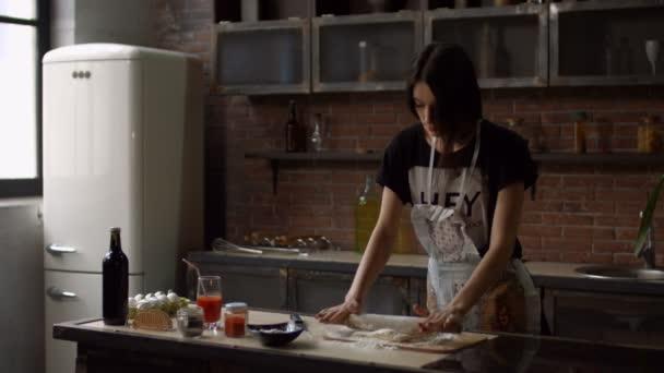 Frau rollt Teig zu Hause mit Nudelholz aus