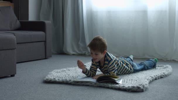 Malý chlapec kreslení vleže na podlaze doma