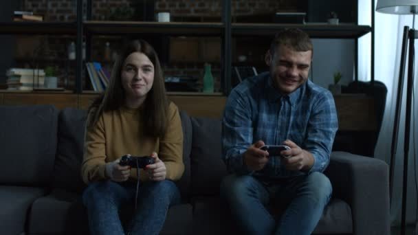 Happy couple playing video games on console
