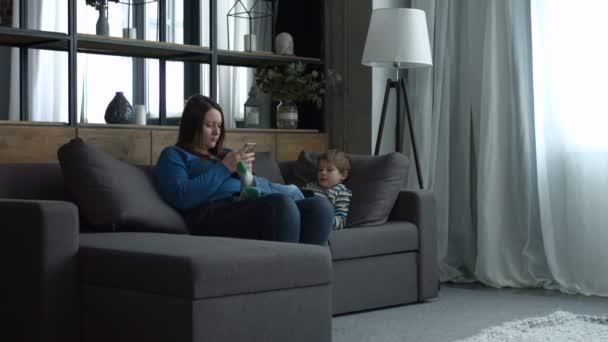 Máma a dítě relaxační na gauči s digitálními zařízeními