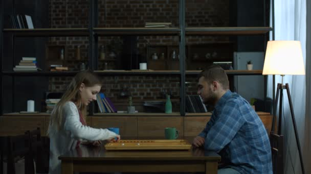 Young positive couple playing backgammon at home