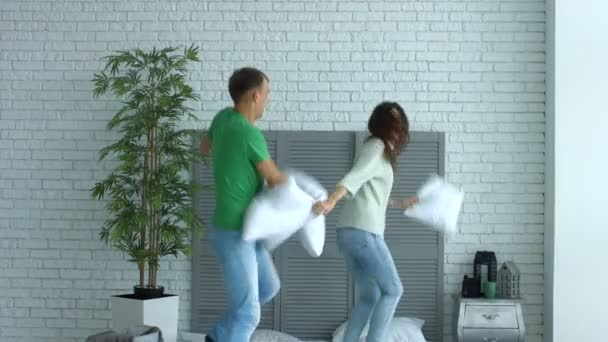 Happy couple having pillow fight in the bedroom