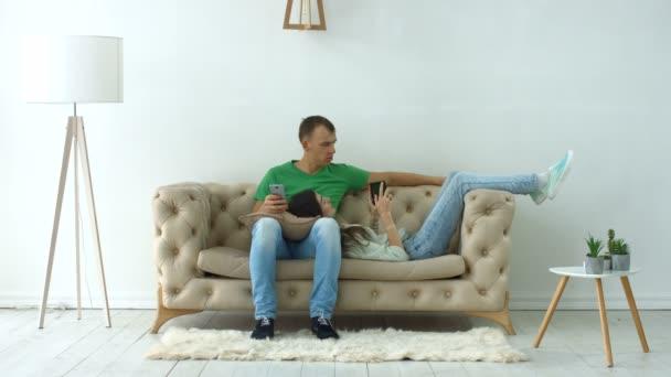 Pár s digitálními zařízeními relaxační na gauči