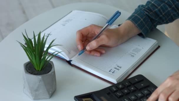 Zenske ruce psaní poznámek a použití kalkulačky