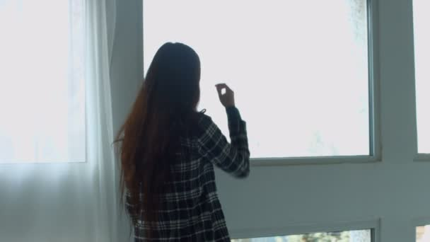 Sensual dreaming woman looking out window