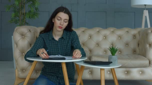 Frustrated woman with expense receipts at home