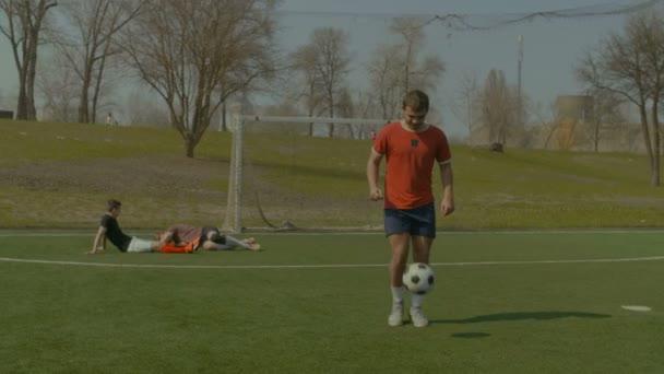 Fotbalista skákací fotbalový míč s nohama