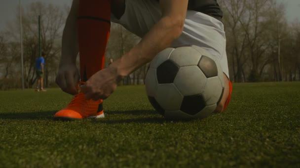 Fotbalista vázání tkaničky na fotbalovém hřišti
