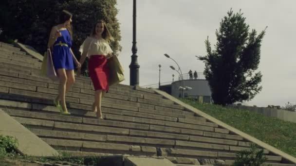 Ženy s nákupníma taškama po schodech dolů