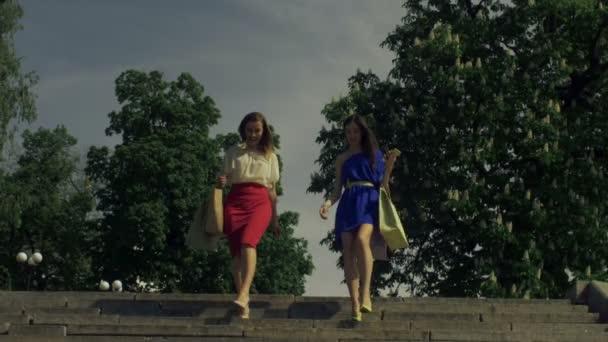 Joyful women with shopping bags going downstairs