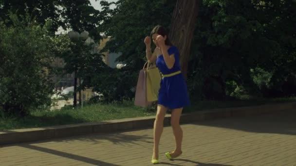 Elegantní žena kroucení kotníku při chůzi na ulici