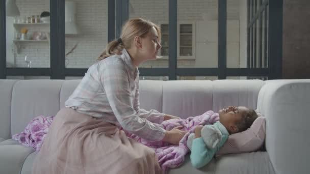 Pečující maminka utěšit ospalý nemocný dítě na pohovce