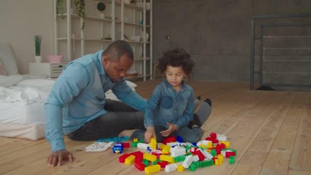 Diverse famiglie che giocano con il costruttore a casa