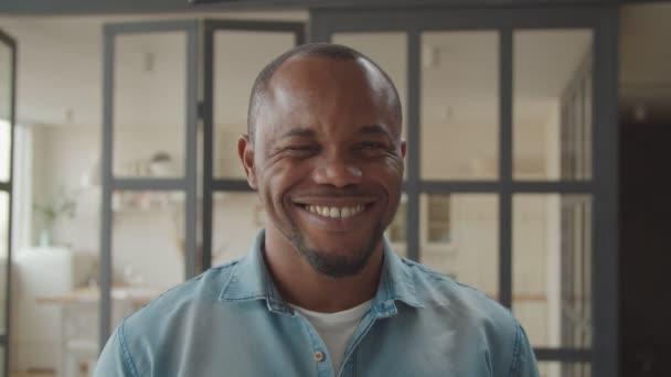 fröhlicher afrikanischer Kerl zwinkert und lächelt verspielt