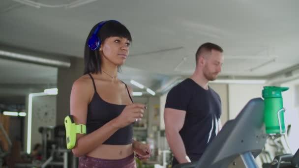 Různí fitness lidé cvičí na běžeckém pásu