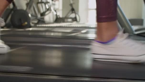 Schlanke Frauenbeine auf Laufband im Fitnessstudio