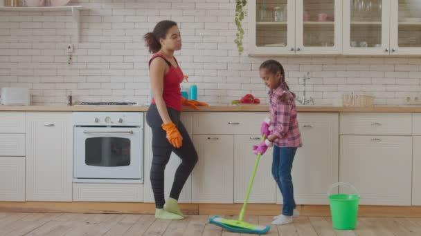 Holčička mytí podlahy s mop v kuchyni