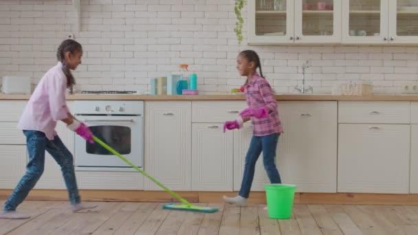 Africké americké sestry tření kuchyňské podlahy