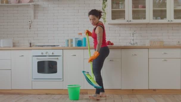 Frau tanzt und singt beim Aufräumen mit Wischmopp