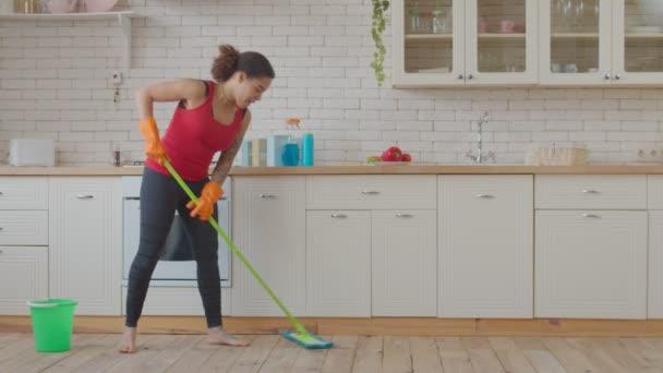 Pozitivní smíšené závod žena vytírání kuchyňské podlahy