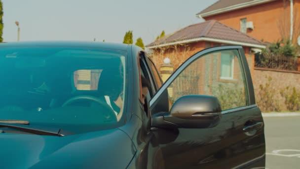 Pozitív női sofőr beszél telefonon az autó közelében