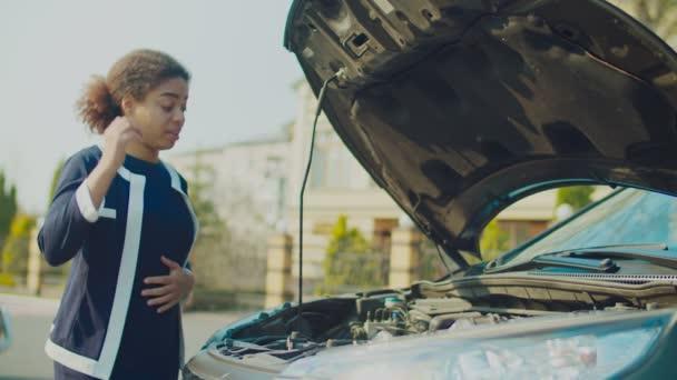 Zavarodott nő néz törött autó motor az utcán