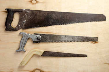 three saws lying on a sheet of plywood. vintage.