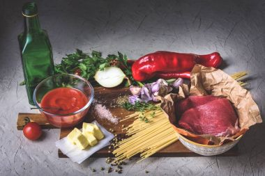 close-up view of raw meat , uncooked spaghetti, pepper, onion, butter, tomato sauce and bottle of oil on cutting board