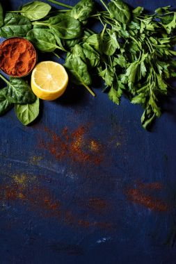 top view of lemon, red pepper, parsley and basil on blue