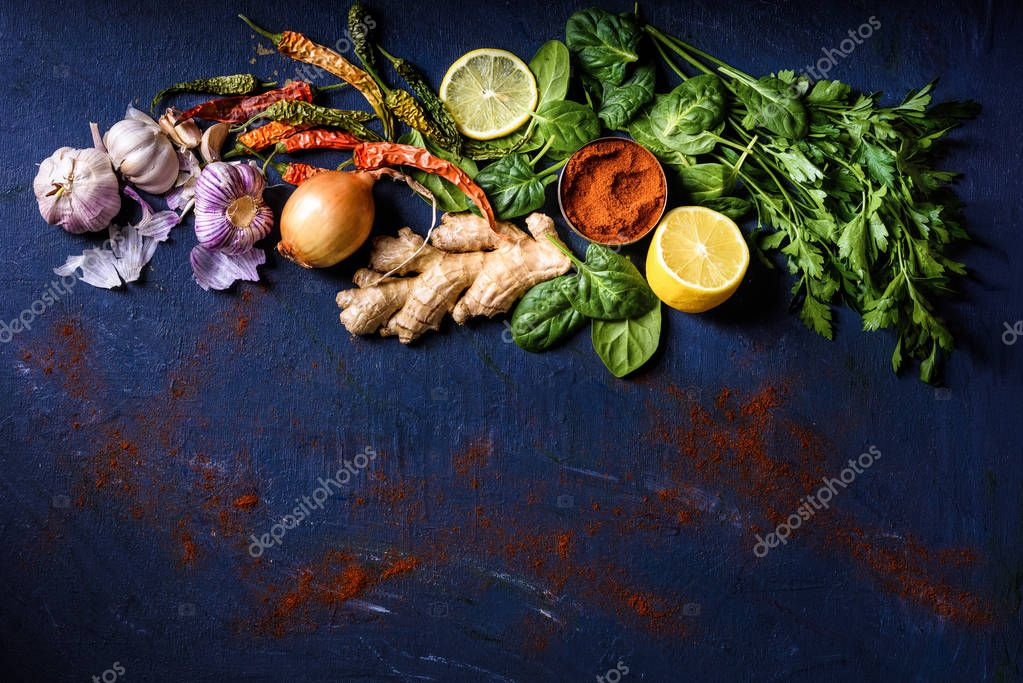 top view of parsley, basil, lemon, peppers, onion, garlic and ginger on blue