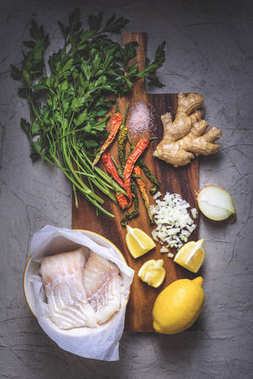 top view of raw fish in bowl, parsley, peppers, salt, onion, lemon and ginger on wooden cutting board