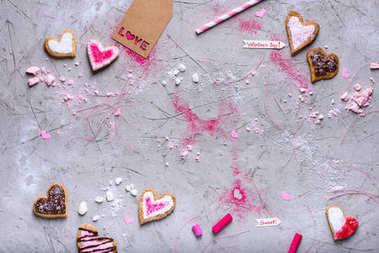 top view of heart shaped valentines cookies with love tag on grey surface with copy space
