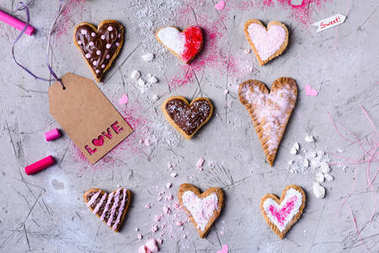 top view of sweet heart shaped cookies with love tag on grey cracked surface