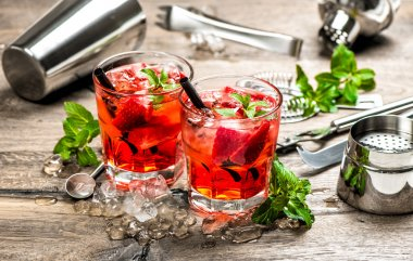 Red drink with strawberry, mint leaves, ice. Cocktail accessorie