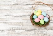 Húsvéti tojás dekorációs fészekben fából készült háttér