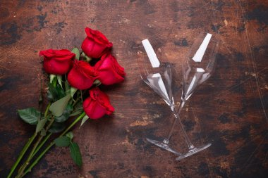 Red rose flowers bouquet and champagne glasses on wooden background Valentine's day greeting card Copy space Top view