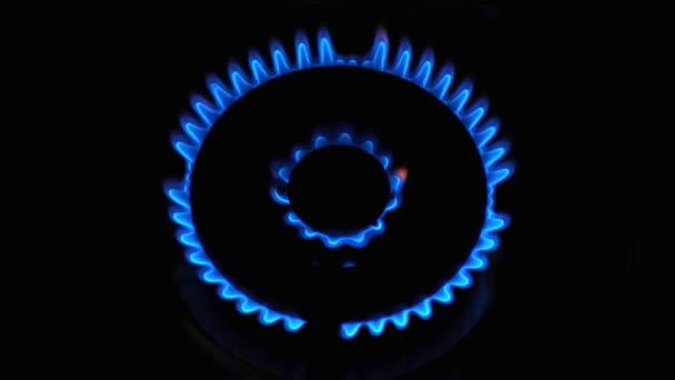 blaue Flamme eines Gasherdes auf schwarzem Hintergrund. Gas einschalten. Erdgaszündung, Nahaufnahme