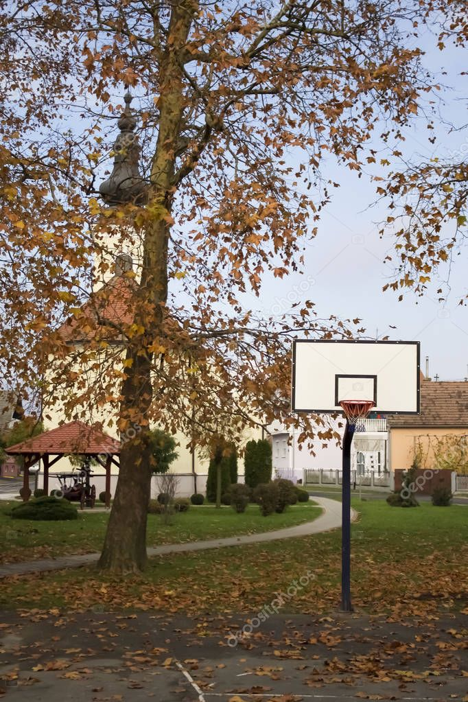 Empty basketball court in autumn covered with yellow leaves and church hiding behind tree