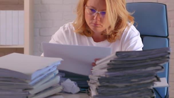 Přepracovaný podnikatel pracující v kanceláři a provádějící výpočty, její stůl je pokryt papírováním.