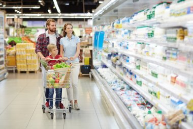 Couple and their son buying products in supermarket