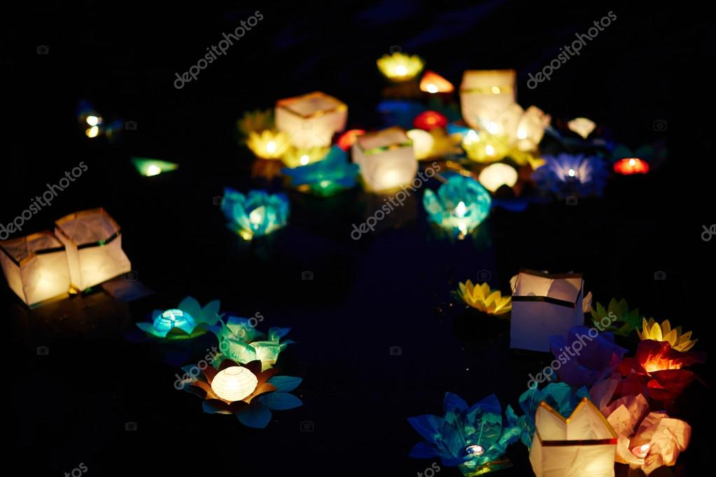 Paper flowers with candles floating on water
