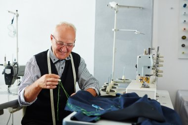 Professional tailor sewing clothes