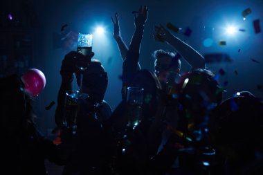 Group of energetic friends dancing in nightclub
