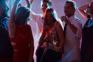 Cheerful friends dancing at disco party