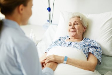 Woman supporting her grandmother in hospital bed