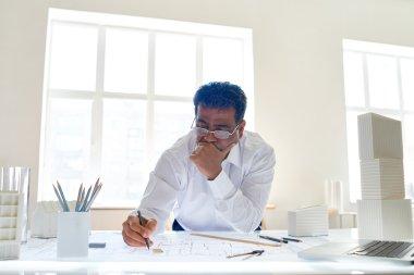 Businessman looking at engineering sketch